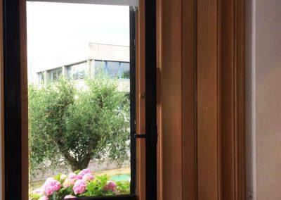 Porta a soffietto in legno su finestra